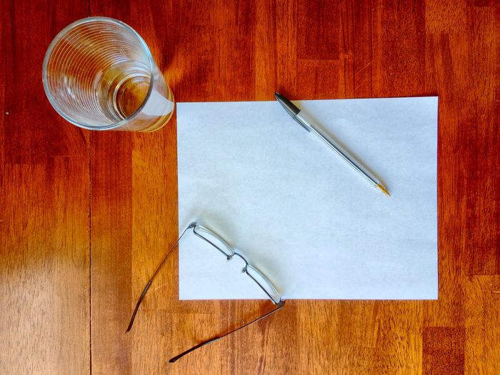 High angle view of a pen with paper on table