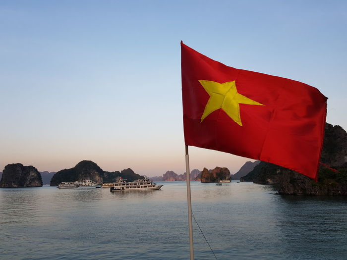 Scenic view of flag by sea against clear blue sky