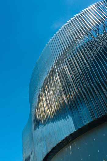 Low angle view of metal against blue sky