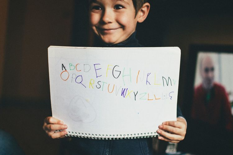 Cute little boy smiling while holding alphabet book
