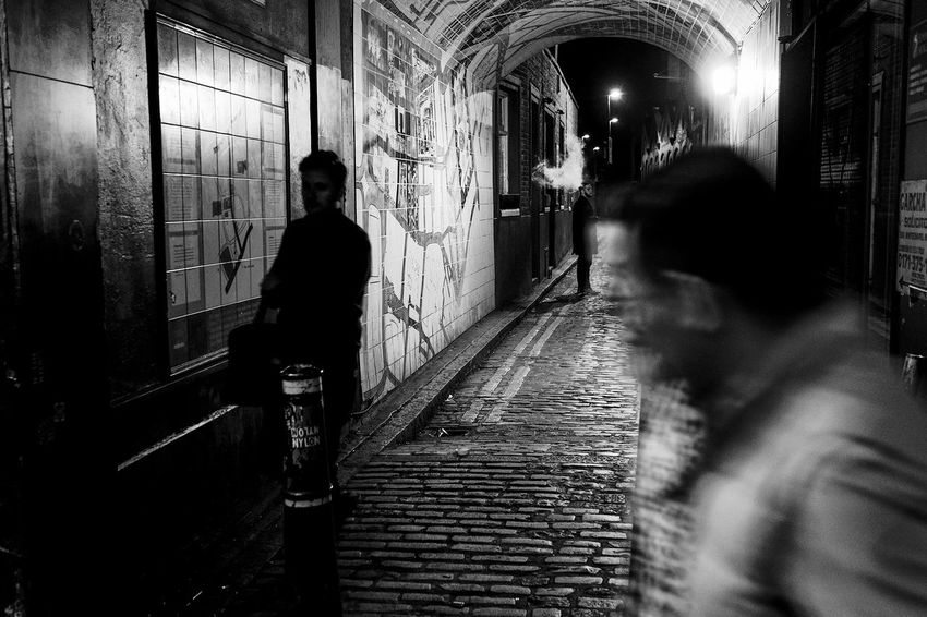 A little alley that leads to Gunthorpe Street in East London. Next to the White Hart Pub this alleyway is one of the places Jack the Ripper carried out his grizzly deed. Dark London Macabre Smoking Winter Adult Alley Illuminated Jack The Ripper Men Moody Night People Real People Street Street Photography Streetphoto_bw Streetphotography Tunnel Walking