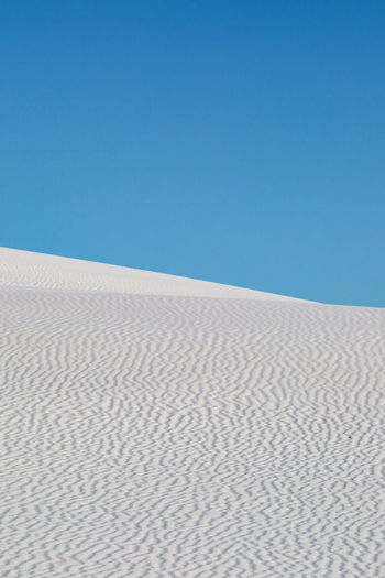 White gypsum sand dunes against a clear blue sky, in White Sands National Monument, New Mexico Sky Sand Clear Sky Desert Blue Land Scenics - Nature Sand Dune Landscape Climate Tranquility Arid Climate Nature Tranquil Scene Environment Pattern No People Copy Space Beauty In Nature Day Outdoors New Mexico White Sands National Monument Copy Space Contrast