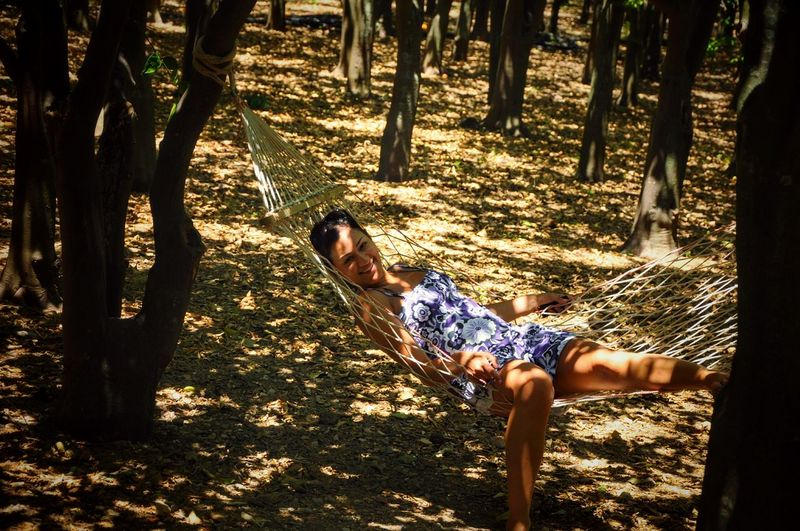 Portrait Of Woman Relaxing In Hammock At Park