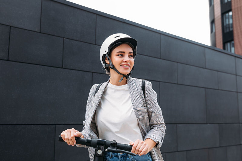 Portrait of beautiful young woman standing on bicycle