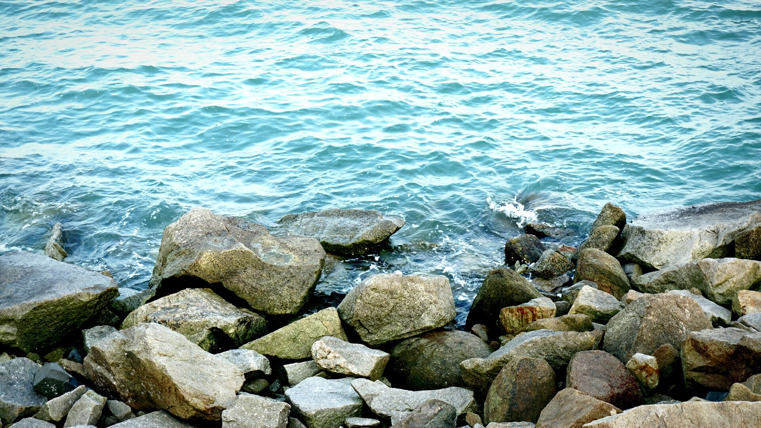 water, rock - object, sea, stone - object, pebble, nature, stone, tranquility, rock, high angle view, beauty in nature, shore, beach, rippled, day, outdoors, scenics, no people, textured, tranquil scene