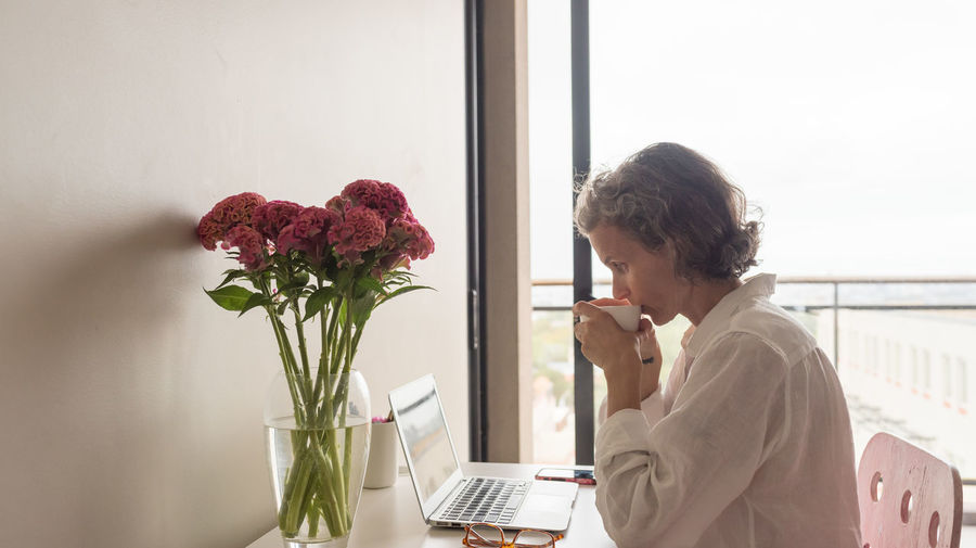 Middle aged woman in home office One Person Flower Flowering Plant Plant Indoors  Computer Freshness Laptop Nature Wireless Technology Lifestyles Window Beauty In Nature Sitting Table Adult Technology Real People Mature Adult Using Laptop Flower Arrangement