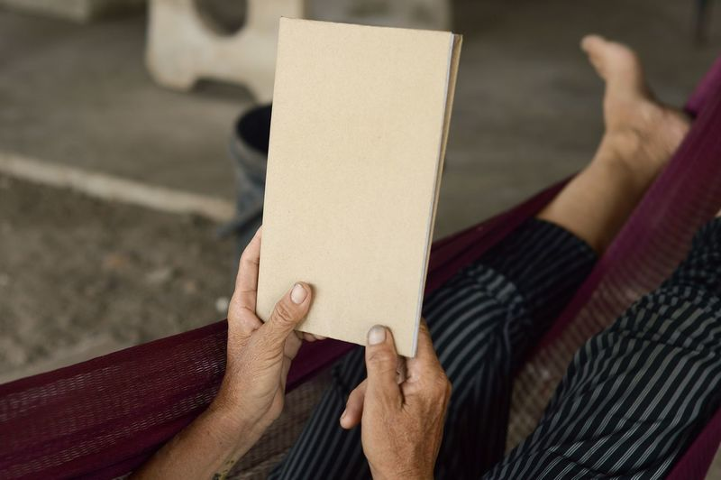 Low Section Of Woman Holding Notebook