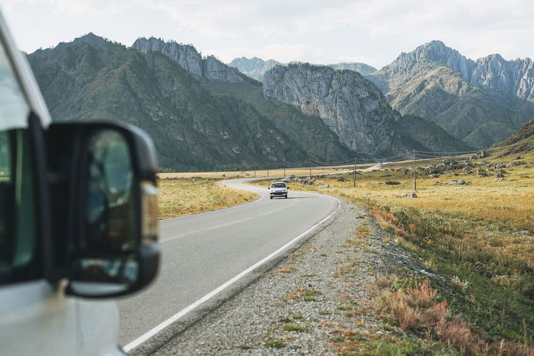 Parked car on the auto road against beautiful mountain landscape, chemalsky tract, altai