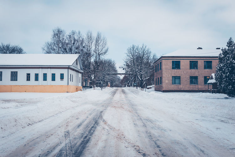Snow covered road by buildings against sky