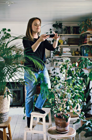 Woman photographing while standing on potted plant