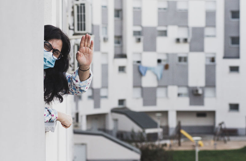Portrait of woman wearing mask waving at balcony