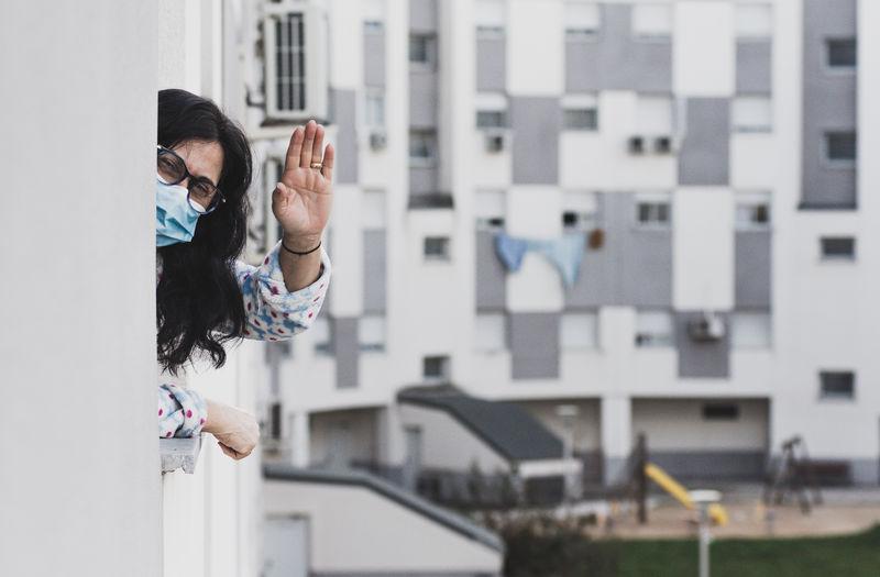 Portrait of woman wearing mask waving at balcony