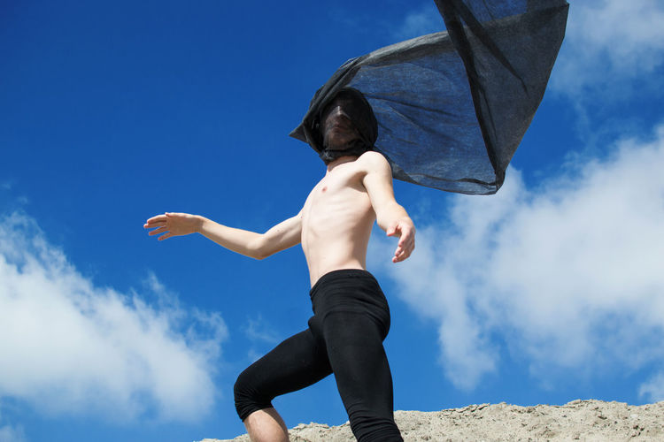 Low angle view of shirtless man with black fabric