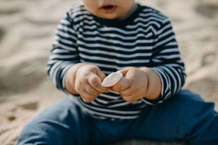 Midsection of cute boy playing with sea shell on beach