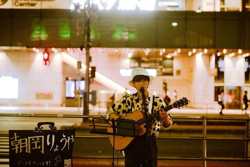 Man playing guitar on illuminated stage
