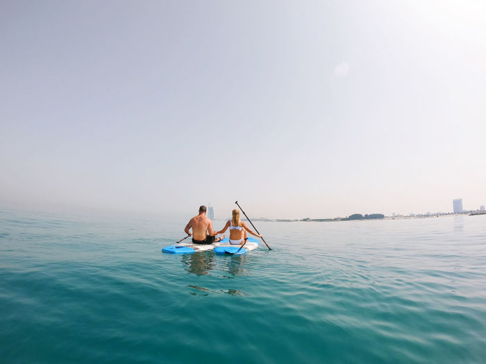 People on paddle board in sea against sky