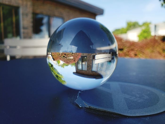 Close-up of crystal ball against building in city