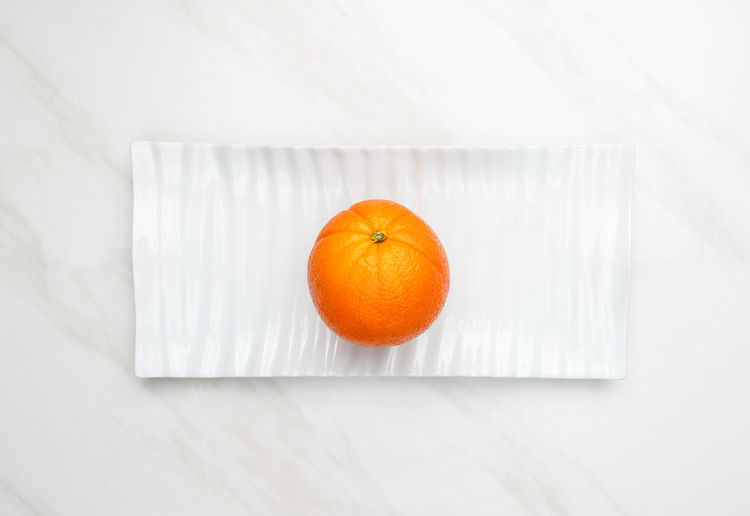 High angle view of orange fruit on white table