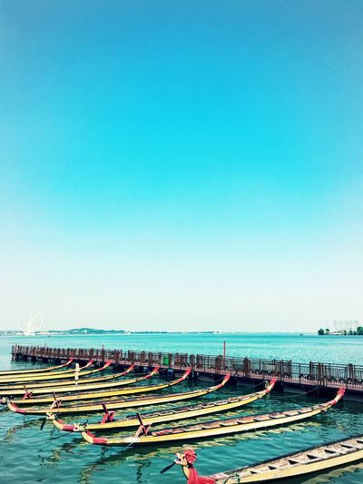 Row of longtail boats moored in sea against sky