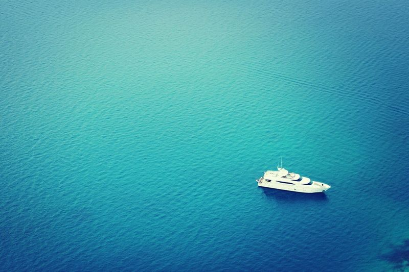 High angle view of lone boat in calm blue sea