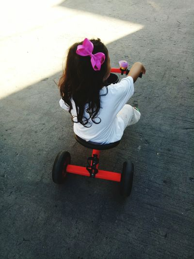 High angle view of girl riding tricycle on concrete