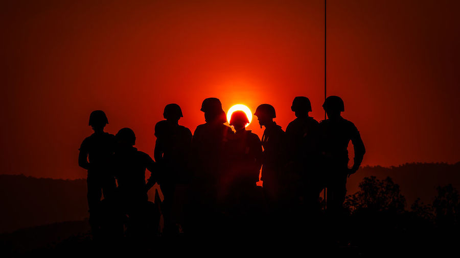 Beauty In Nature Group Of People Land Lifestyles Men Nature Orange Color Outdoors People Real People Silhouette Sky Soldiers Uniform Standing Sun Sunlight Sunset