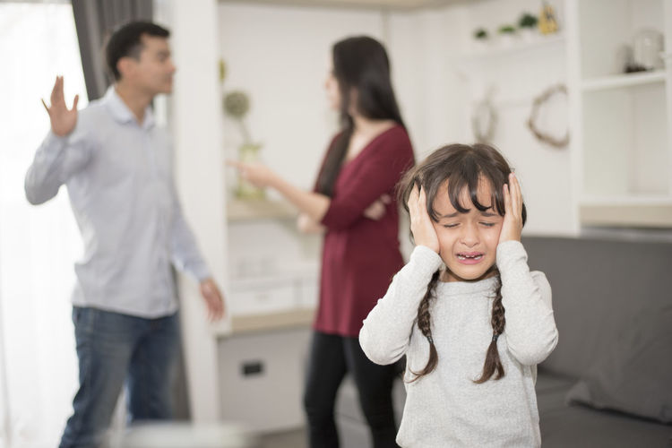 Close-up of girl crying while parents fighting in background at home