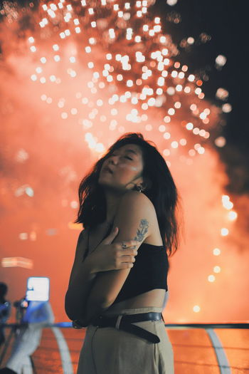Young woman posing while standing against firework display