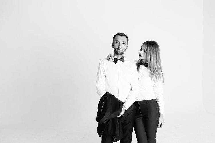 Elegant couple standing against white background