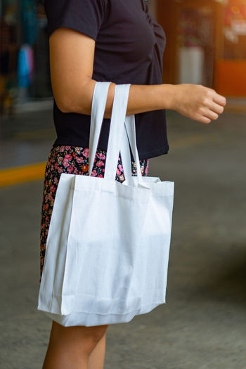 Midsection of woman holding shopping bag