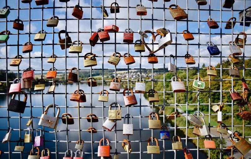 Full frame shot of padlocks hanging on fence against sky