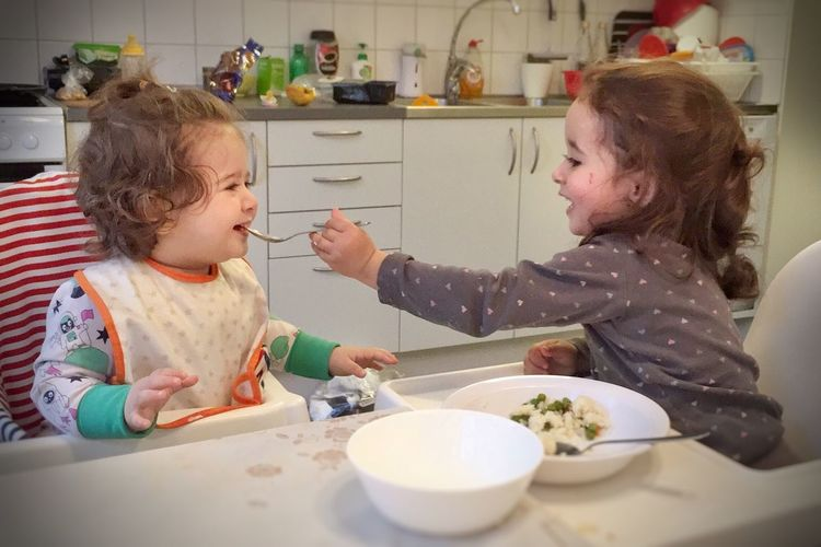 Domestic Kitchen Two People Domestic Room Kitchen Togetherness Childhood Girls Indoors  Plate Baby Family Domestic Life Bowl Home Interior Toddler  Females Child Food And Drink Eating Bonding Genuine Genuine Moment Genuine Smile Compassion Sisters