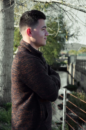 Profile View Of Thoughtful Young Man Standing Against Trees