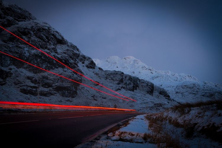 Light trails on road leading towards snowcapped mountains at dusk