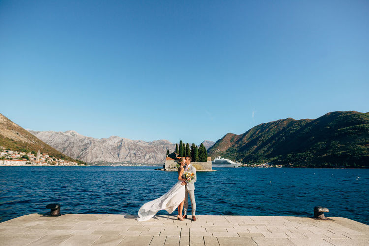 Full length of couple embracing while standing against lake