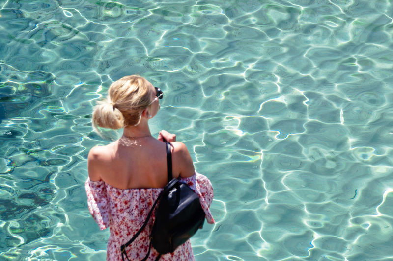 High angle view of woman standing by swimming pool