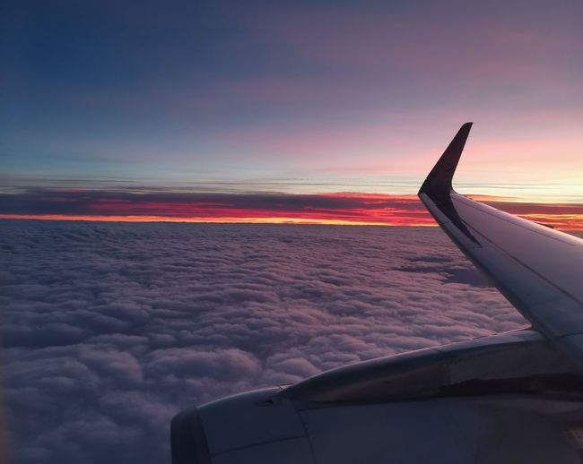 Airplane flying over sea against sky during sunset