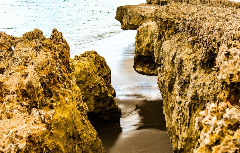 Rock formation Water Sea Beach Rock - Object Reflection Rushing Pebble Beach Wave Rocky Coastline Tide Crashing Rugged