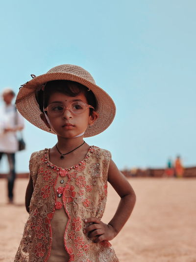 Cute girl wearing hat and eyeglasses looking away while standing at beach against sky