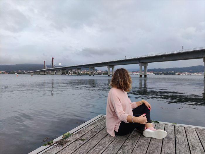 Rear view of woman sitting on bridge against sky