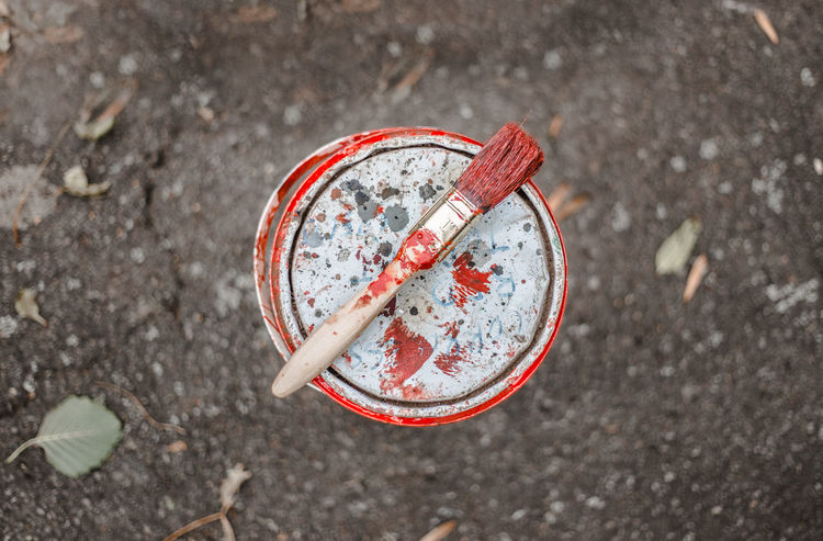 Paint brush resting on top of tin during an outdoor project DIY Decorating Pain Paint Paint Brush Close-up Day Flat Lay Freshness High Angle View No People Outdoors Paint Pots Paint Splash Project Red Paint Tin Of Paint