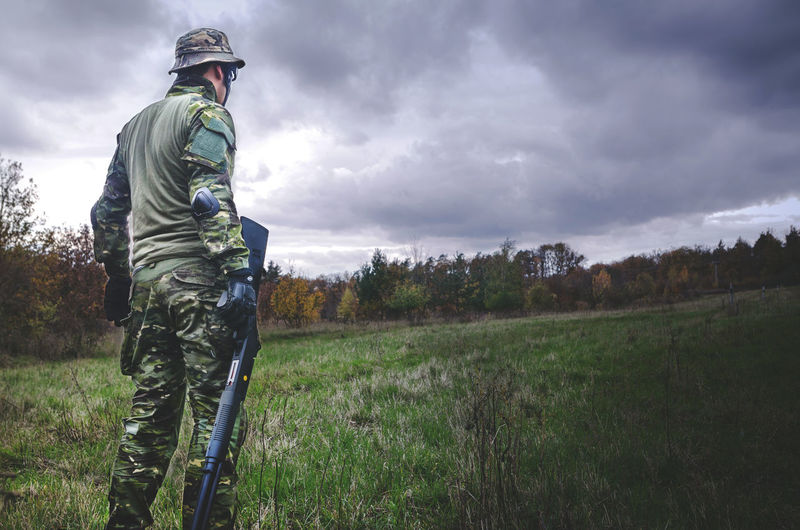 Rear view of soldier with rifle standing on grass against sky