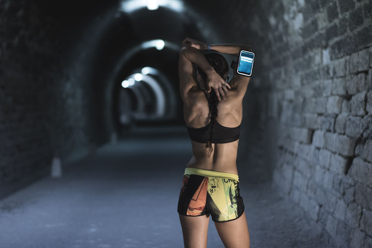 young woman stretching in tunnel Rear View Warming Woman Attractive Backgrounds Braided Hair Female Healthy Lifestyle Indoors  Jogging Lifestyles Muscular Build person Recreational Pursuit Sexygirl Sport Sports Stretching Telephone Line Tunnel Young Adult