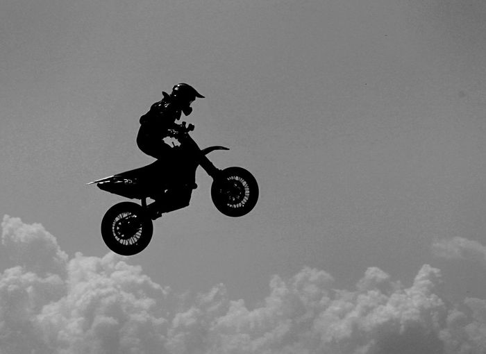 Side view of motocross racer performing mid-air against sky