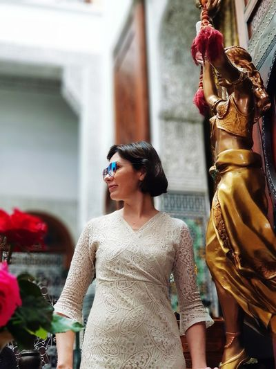 Woman standing by statue