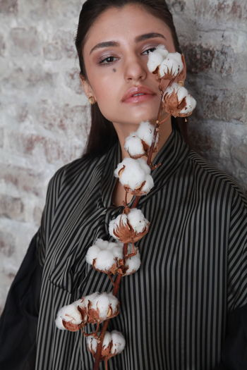 Close-up portrait of young woman holding cotton against wall