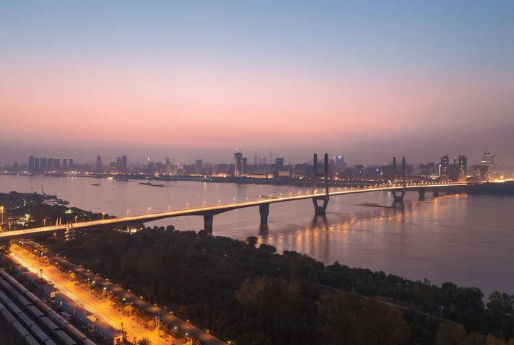 Illuminated Bridge Over River Against Sky At Sunset