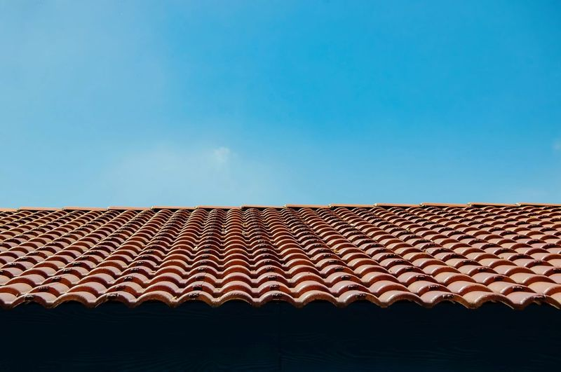 Low Angle View Of Tiled Roof Against Blue Sky
