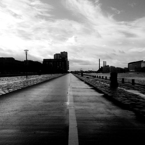 Empty road against cloudy sky