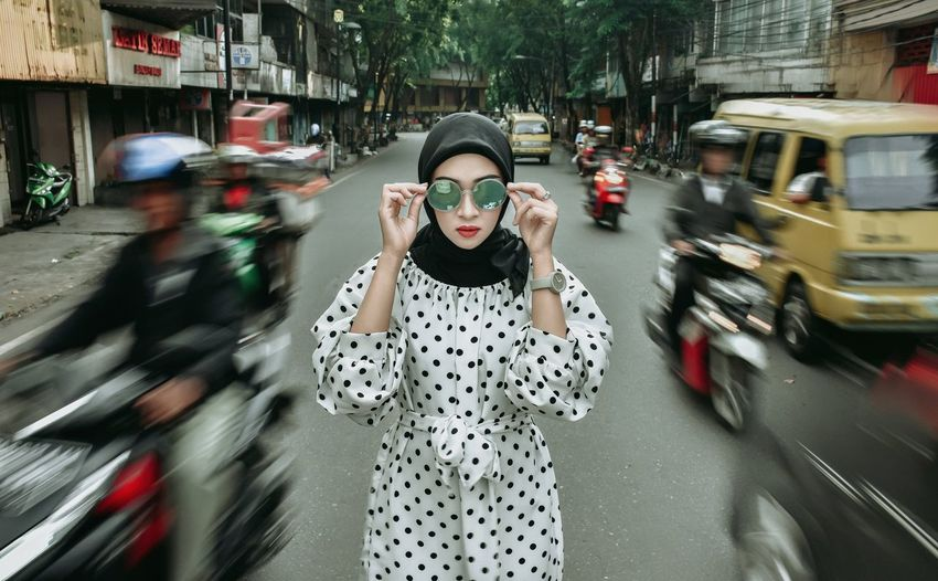 Blurred motion of woman on road in city